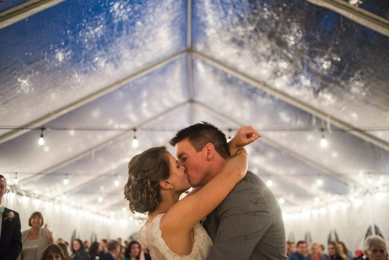 couple kissing under clear tent during rain