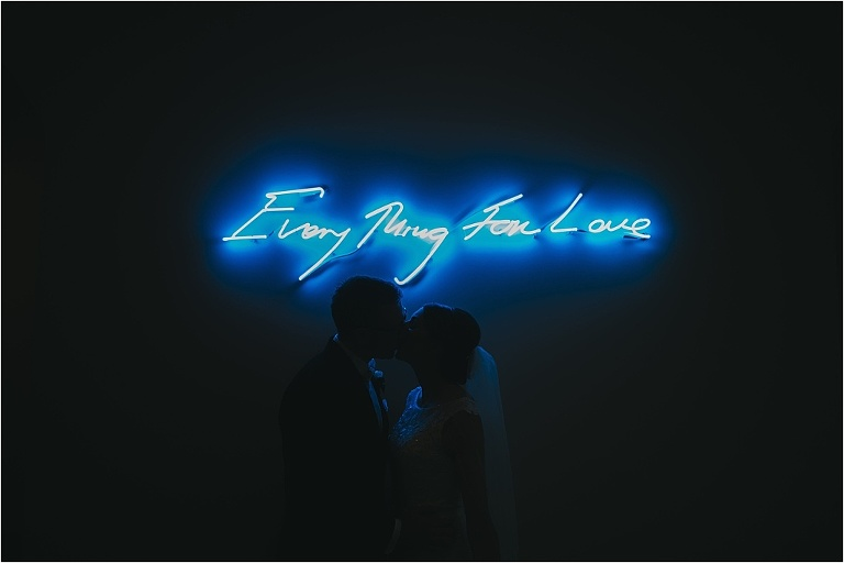 alfond inn indoor portrait with neon light artwork behind kissing wedding couple