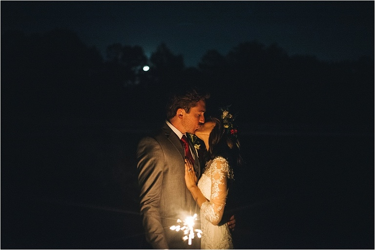 intimate sparkler portrait of kissing couple outside night time wedding portrait