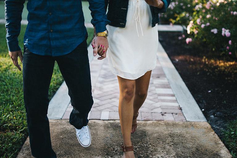 couple holding hands and walking through leu gardens
