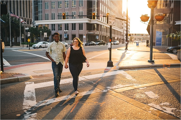 modern couple having an engagement session walking the street near the grand bohemian hotel in downtown orlando