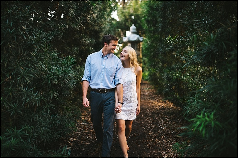 couple walking through the gardens near bok tower laughing candidly