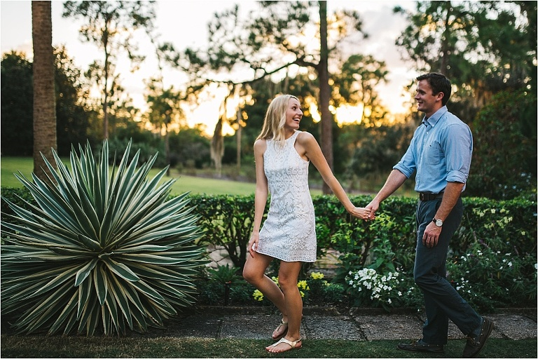 couple holding hands and walking through bok tower gardens near pinewood estates during sunset