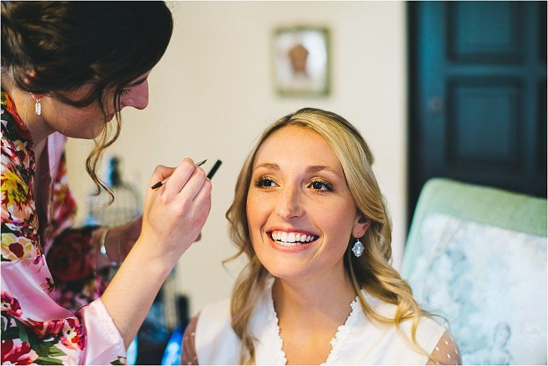 bride smiling as she's getting her makeup done