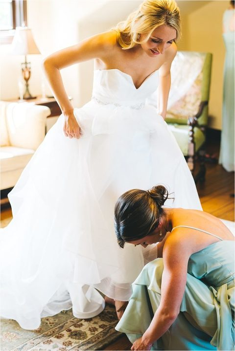 maid of honor helping bride with her badgley mischka