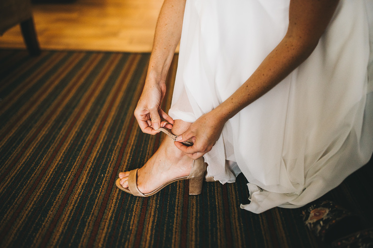 bride putting on shoes before heading to ceremony site